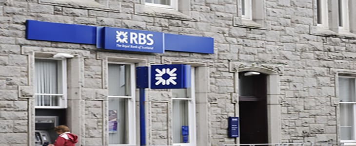 """Castle Douglas, Scotland - August, 30 2011: A member of the public using an ATM at the Castle Douglas branch of The Royal Bank of Scotland. The Royal Bank of Scotland was one of the banks that had to be bailed out by the Goverment during the recent economic crisis"""