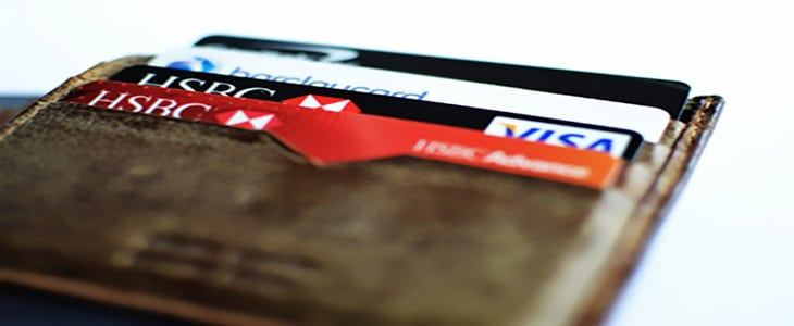 Close up shot of a brown wallet containing HSBC, Barclaycard and Capital One credit and debit cards.